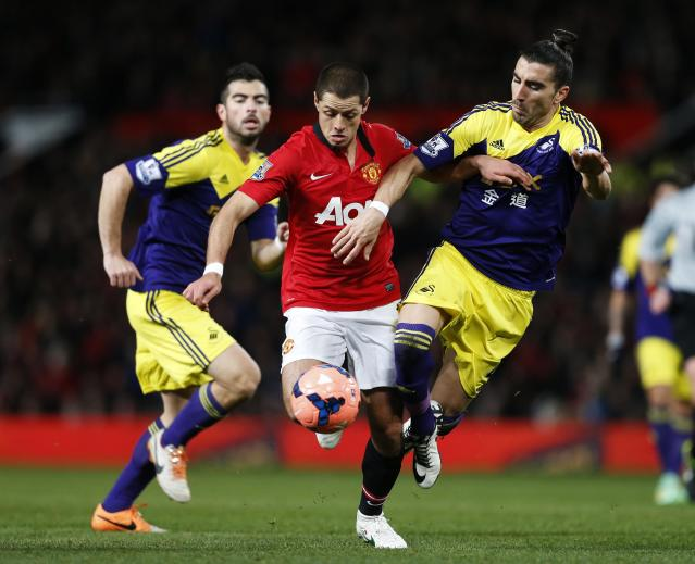 Manchester United's Javier Hernandez (C) is tackled by Swansea City's Chico Flores (R) during their English FA Cup third round soccer match at Old Trafford in Manchester, northern England January 5, 2014. REUTERS/Russell Cheyne (BRITAIN - Tags: SPORT SOCCER)
