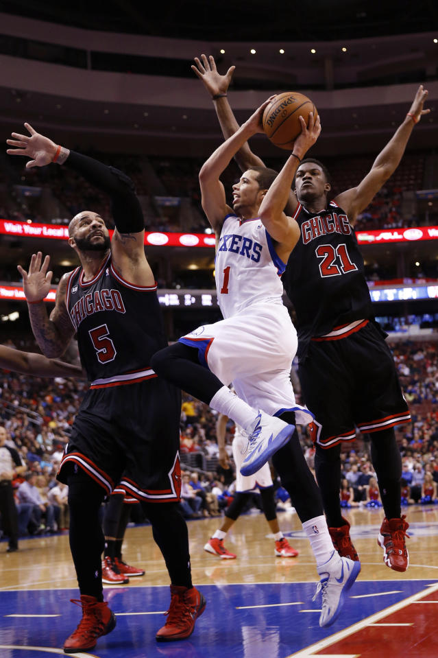 Philadelphia 76ers' Michael Carter-Williams, center, goes up for a shot against Chicago Bulls' Carlos Boozer, left, and Jimmy Butler during the second half of an NBA basketball game, Wednesday, March 19, 2014, in Philadelphia. Chicago won 102-94. (AP Photo/Matt Slocum)
