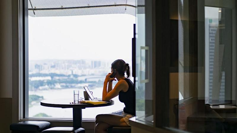 A woman answers a call while looking out the window in co-working space The Great Room's Centennial Tower location in Singapore