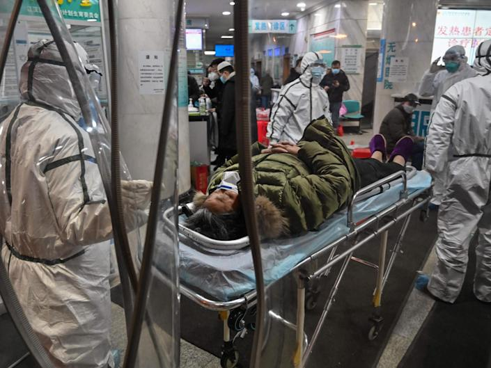 Medical staff members wearing protective clothing to help stop the spread of a deadly virus which began in the city, arrive with a patient at the Wuhan Red Cross Hospital in Wuhan on 25 January: AFP via Getty Images