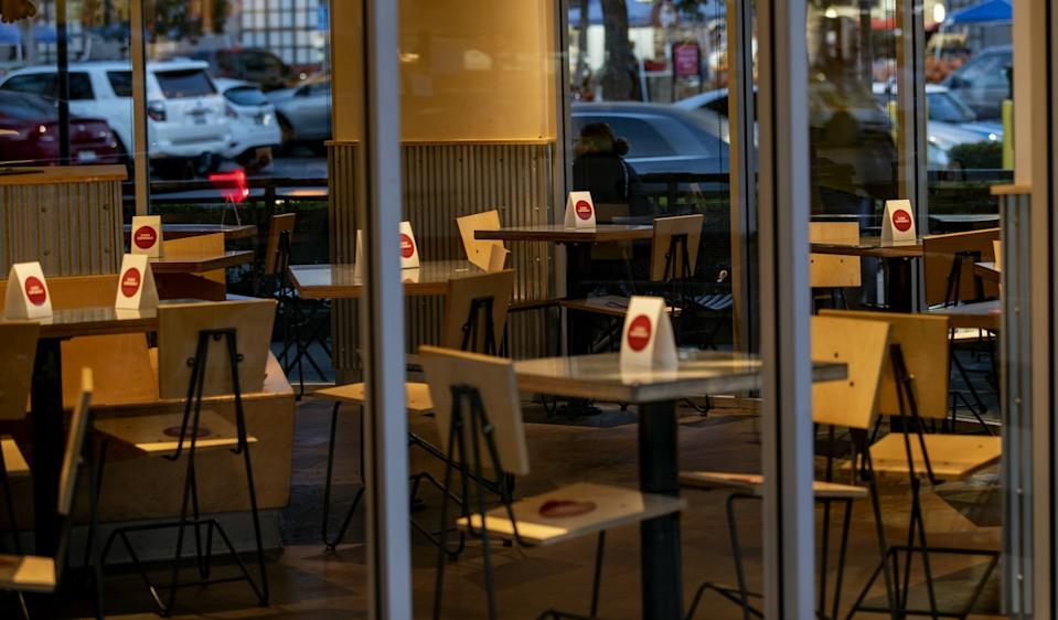 Signs are placed on tables that are off-limits to diners inside a Chipotle restaurant in Riverside.