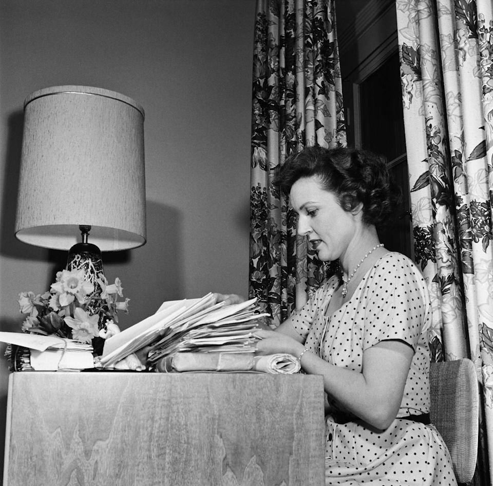 <p>Hollywood's <em>Golden Girl </em>sits at her desk as she sorts through mail and packages. </p>