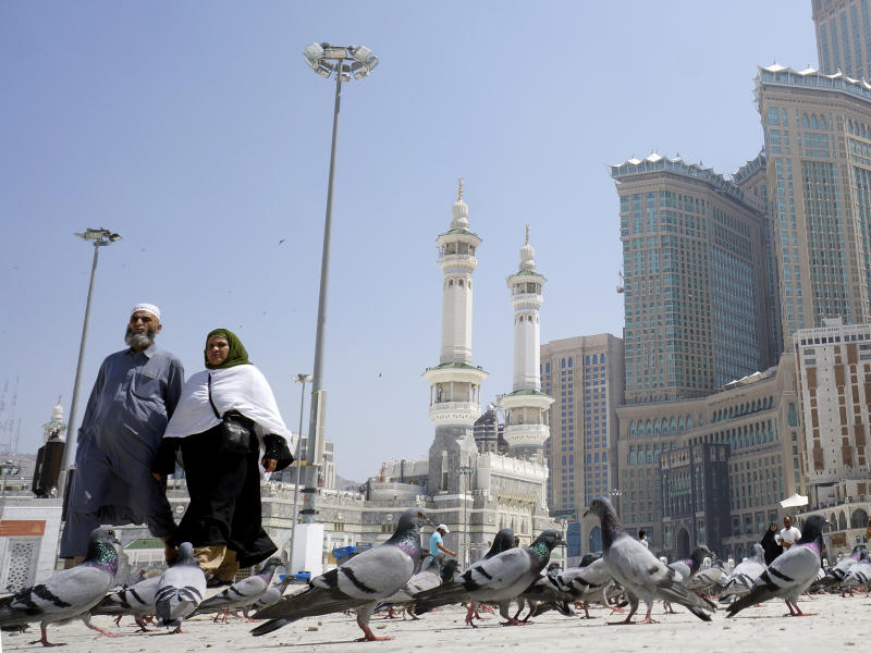 Muslim worshippers walk past pigeons after the noon prayers outside the Grand Mosque, in the Muslim holy city of Mecca, Saudi Arabia, Saturday, March 7, 2020. Saudi Arabia announced there would be no spectators for sports competitions and games starting Saturday in order to combat the spread of the virus. The kingdom has taken unprecedented measures against the virus' spread, including halting all pilgrimage in Mecca, Islam's holiest site.  (AP Photo/Amr Nabil)