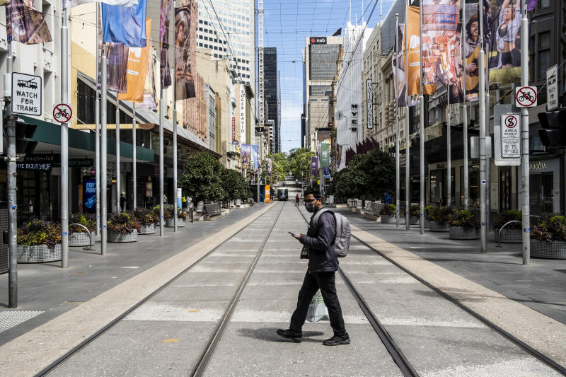 A man wearing a face mask as a preventive measure holds a cellphone while crossing Bourke street.Under the stage 4 restriction of lockdown due to the second wave of Covid 19, the city appears to be desolate with only a few people around for essential reasons. This harsh lockdown is unlikely to be eased on Sunday as expected. (Photo by Diego Fedele/SOPA Images/LightRocket via Getty Images)