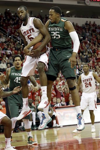 North Carolina State's C.J. Leslie (5) and Miami's Kenny Kadji (35) struggle for a rebound during the first half of an NCAA college basketball game in Raleigh, N.C., Saturday, Feb. 2, 2013. (AP Photo/Gerry Broome)