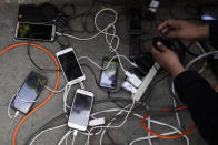 Migrants charge their phones from a generator brought by a local church at a makeshift camp of migrants at the border port of entry leading to the United States, Wednesday, March 17, 2021, in Tijuana, Mexico. The migrant camp shows how confusion has undercut the message from U.S. President Joe Biden that it's not the time to come to the United States. Badly misinformed, some 1,500 migrants who set up tents across the border from San Diego harbor false hope that Biden will open entry briefly and without notice. (AP Photo/Gregory Bull)