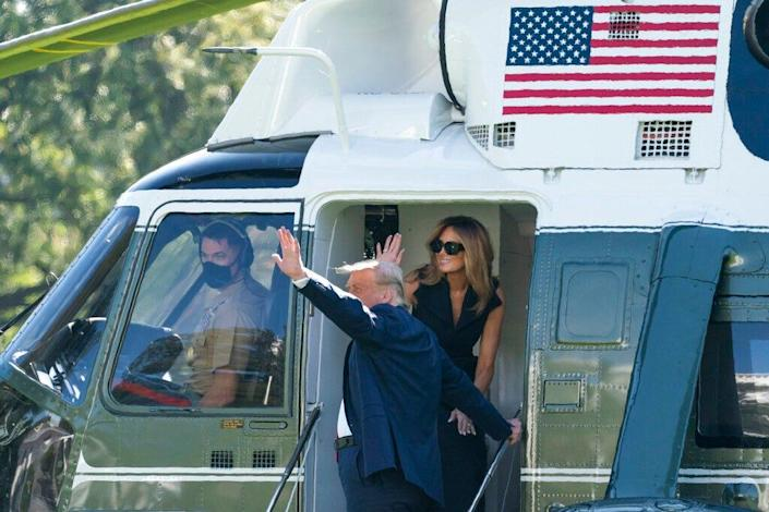 President Donald Trump, accompanied by first lady Melania Trump, wave at supporters as they board Marine One on the South Lawn of the White House on Oct. 22, 2020. Trump was headed to Nashville, Tenn., for a debate.