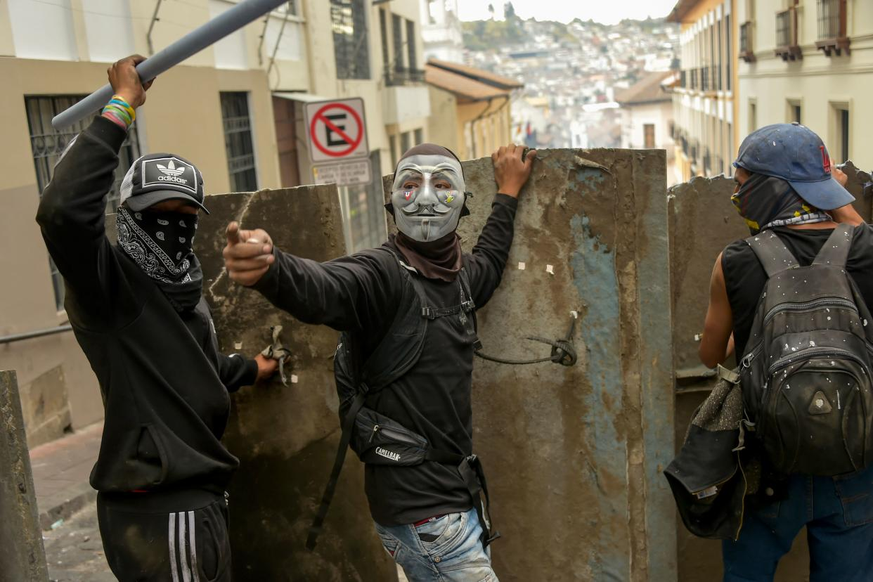 Demonstrators protect themselves with makeshift shields during clashes with riot police in Quito, as thousands march against Ecuadorean President Lenin Moreno's decision to slash fuel subsidies, on Oct. 9, 2019. (Photo: Rodrigo Buendia/AFP via Getty Images)