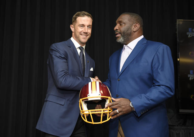 Newly signed Washington Redskins quarterback Alex Smith, left, shakes hands and poses with Doug Williams, the NFL football team's senior vice president of player personnel, during a news conference Thursday, March 15, 2018, in Ashburn, Va. (AP Photo/Nick Wass)