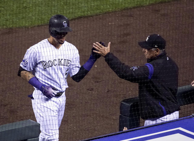 Colorado Rockies' Carlos Gonzalez (5) is congratulated by manager Bud Black after hitting a solo home run against the New York Mets during the fourth inning of a baseball game, Tuesday, June 19, 2018, in Denver. (AP Photo/Jack Dempsey)