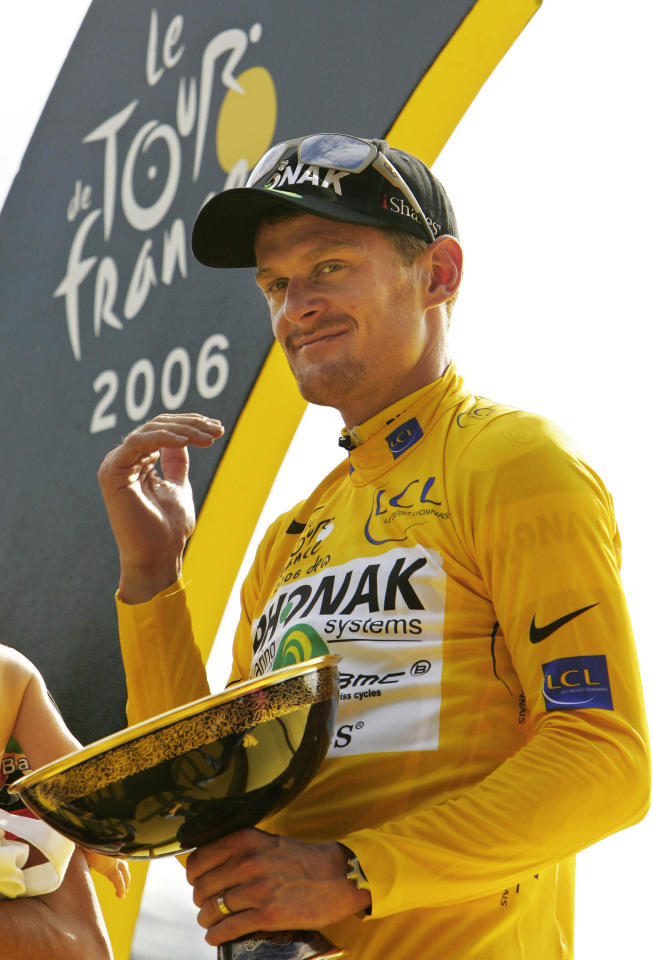 FILE - In this July 23, 2006 file photo, Tour de France winner Floyd Landis of the U.S. holds his trophy on the podium after the final stage of the 93rd Tour de France cycling race in Paris. A French court on Thursday, Nov. 10, 2011 convicted American cyclist Floyd Landis in absentia for his role in hacking into the computers of a French doping lab. (AP Photo/Peter Dejong, File)