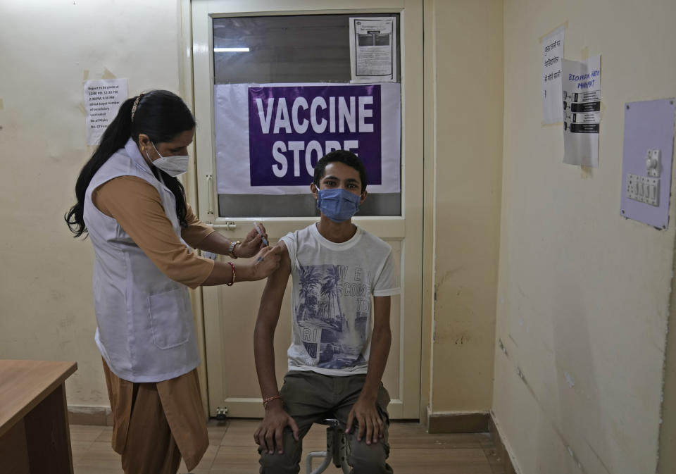 A health worker administers the vaccine for COVID-19 at a vaccination center in New Delhi, India, Tuesday, Sept. 21, 2021. India, the world's largest vaccine producer, will resume exports and donations of surplus coronavirus vaccines in October after halting them during a devastating surge in domestic infections in April, the health minister said Monday. (AP Photo/Manish Swarup)