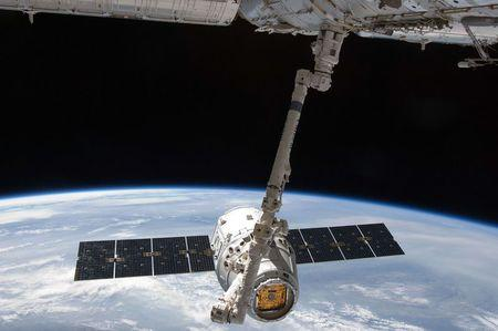 The SpaceX Dragon commercial cargo craft is grappled by the Canadarm2 robotic arm at the International Space Station in this NASA handout photo