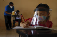 Wearing a mask and a face shield to curb the spread of the new coronavirus, 10-year-old Jade Chan Puc writes in her workbook during the first day of class at the Valentín Gomez Farias Indigenous Primary School in Montebello, Hecelchakan, Campeche state, Monday, April 19, 2021. Campeche is the first state to transition back to the classroom after a year of remote learning due to the pandemic. (AP Photo/Martin Zetina)