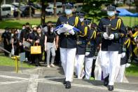 A military honour guard carries the urn of former Philippine President Benigno Aquino in Quezon City
