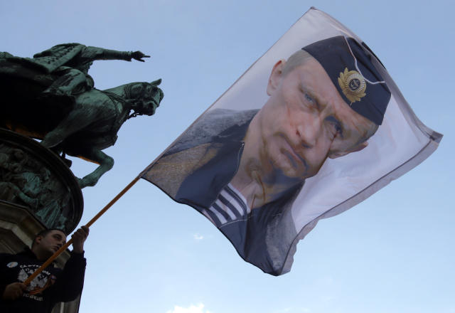 FILE - In this Saturday, Sept. 24, 2016, file photo, a man waves a flag showing Russian President Vladimir Putin, in front of the monument of late Serbian Duke Mihailo Obrenovic, during a meeting where show their support for a referendum in Republika Srpska, in Belgrade, Serbia. Vladimir Putin has accused the U.S. and the West of destabilizing the Balkans with NATO expansion policies as Serbia prepares a hero's welcome for the Russian president. (AP Photo/Darko Vojinovic, File)
