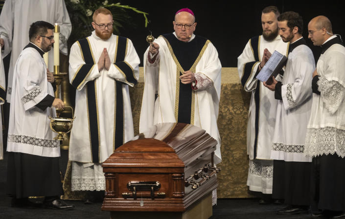 Bishop Carl Kemme of the Wichita Diocese, sprinkles holy water on the casket of Father Emil Kapaun during Kapaun's funeral mass on Wednesday, Sept., 29, 2021 in Wichita, Kan. Kapaun died in a North Korean POW camp in May of 1951. He was posthumously awarded the Medal of Honor in 2013 for his bravery in the Korean War. Kapaun's remains were identified earlier this year returned home to Kansas recently. (Travis Heying/The Wichita Eagle via AP)