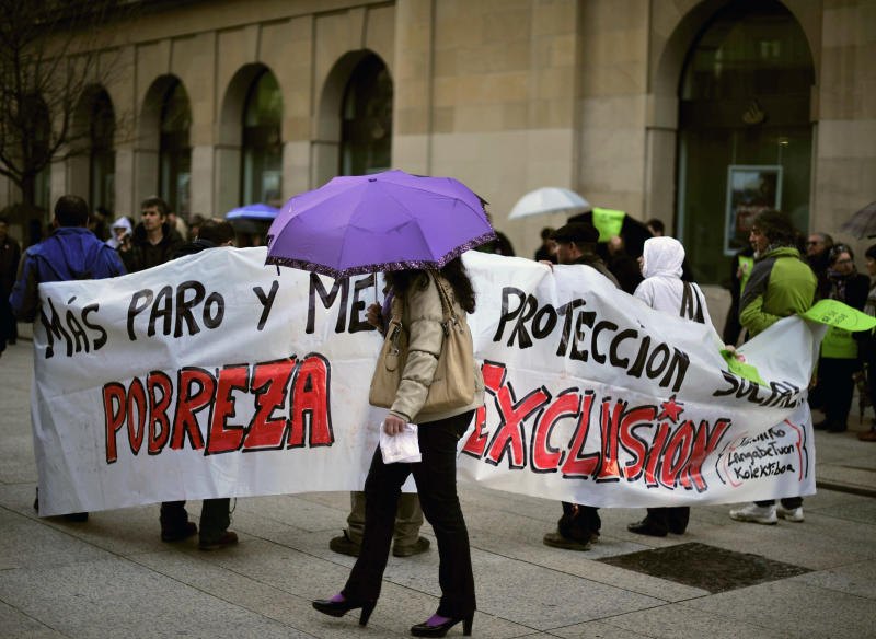 Unemployed people gather on a street and hold a banner reading, ''More unemployment. Less protection. Poverty. Exclusion'' while a woman shelters by the rain  in Pamplona northern Spain on Tuesday, April 2, 2013. Spanish government figures show that the number of people registered as unemployed edged down by a little under 5,000 in March, the first reduction for the month in five years. The scale of the task remains huge though as the number registered as unemployed stands at 5.04 million. Spain is battling to emerge from its second recession in just over three years. (AP Photo/Alvaro Barrientos)