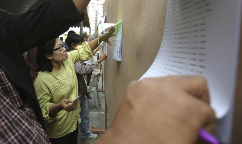 Thai voters check for their name at a polling station in Bangrak district before it was shut down, in Bangkok,Thailand, Sunday, Jan. 26, 2014. Anti-government demonstrators in Thailand swarmed polling stations in the capital Sunday and chained their doors shut to block voters from getting inside, reneging on a pledge not to obstruct advance voting for a contentious general election scheduled for next week. (AP Photo/Sakchai Lalit)
