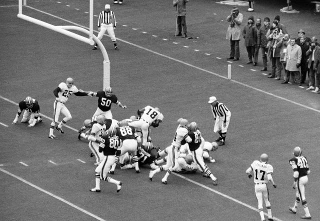 FILE - In this Nov. 15, 1970, file photo, Cincinnati Bengals' Paul Robinson (18) scores the game-winning touchdown from the one-yard-line in the first half of a football game against the Cleveland Browns in Cincinnati. Others shown are Bengals' Jess Phillips (30) and Browns' Joe Jones (80), Jim Houston (82), Ron Snidow (88), Walter Johnson (71) and John Garlington (50). The Cincinnati Bengals 14-10 victory over the Cleveland Browns on a snowy, November afternoon in 1970 put Browns new team on equal footing with his old one and made Ohio truly a two-team pro football state. (AP Photo/GS, File)