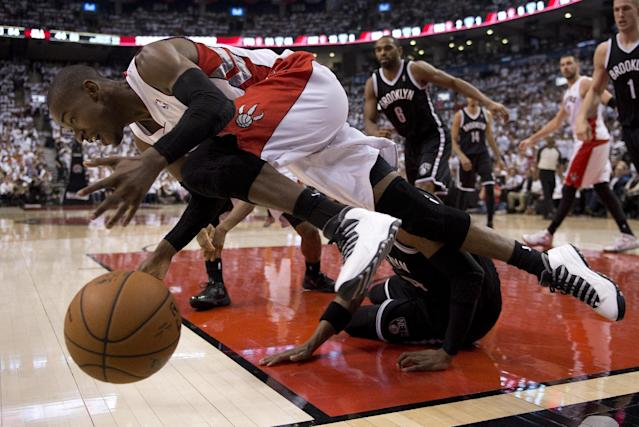 Toronto Raptors guard Terrence Ross tumbles over Brooklyn Nets Paul Pierce during the first half of Game 5 of the opening-round NBA basketball playoff series in Toronto, Wednesday, April 30, 2014. (AP Photo/The Canadian Press, Frank Gunn)