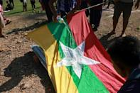 Protesters poured petrol on the Myanmar flag to burn with copies of 2008 constitution during a demonstration against the military coup in Kawkareik township in Myanmar's Karen state
