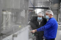 Rabbi Mendel Einhorn, left, looks on as foreman Dave Garthe runs boiling water through and over machinery in preparation for Hanan Products kosher-for-passover production run, Thursday, Jan. 7, 2021, in Hicksville, N.Y. (AP Photo/Seth Wenig)
