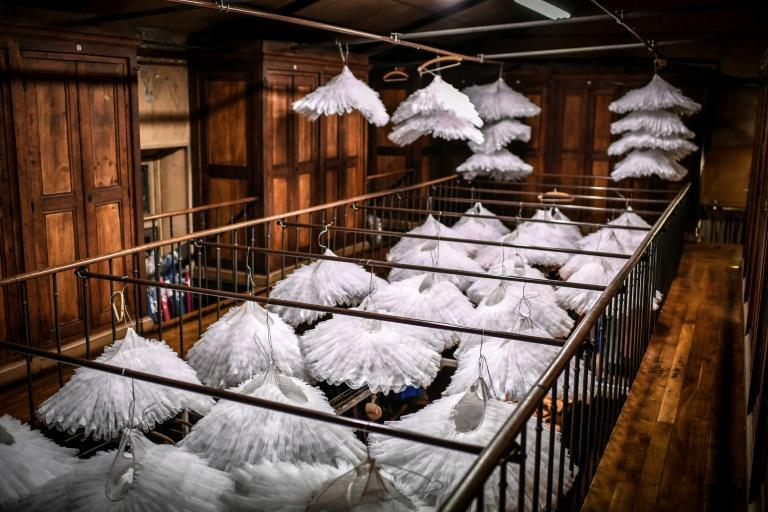 """Dozens of white tutus hanging in a historic room known as """"central"""" at the Paris Opera"""