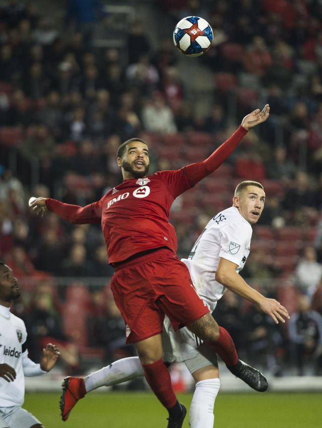 Toronto FC forward Jordan Hamilton, left, eyes then ball against D.C. United midfielder Russell Canouse, right, during the second half of an MLS soccer game, Wednesday, May 15, 2019 in Toronto. (Nathan Denette/The Canadian Press via AP)