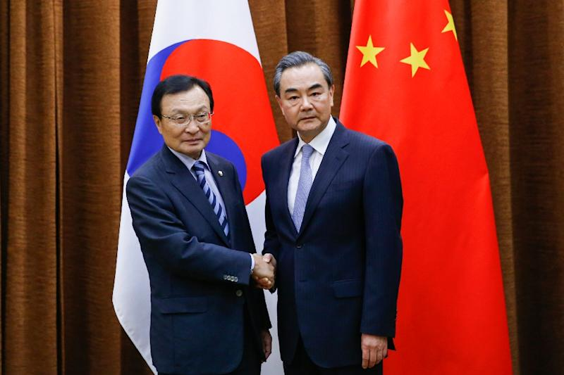 China's Foreign Minister Wang Yi (right) shakes hands with South Korean special envoy Lee Hae-chan at the foreign ministry in Beijing on May 18, 2017