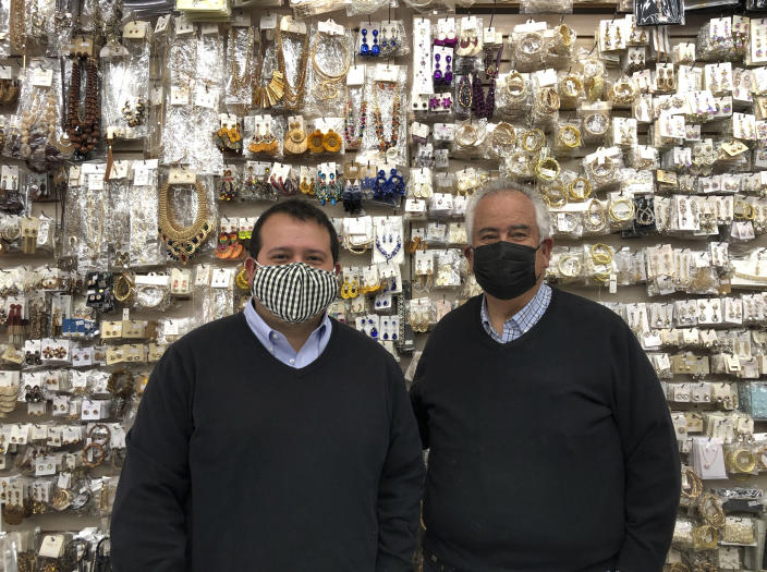 Business owner Greg Kory and his father stand in front of a wall of jewelry at their downtown Nogales, Arizona, store on March 15, 2021. Two of the family's three clothing stores located steps away from the U.S.-Mexico border have been closed for almost a year, with their main customer base, Mexican day-trippers, largely unable to come to the U.S. and shop due to the partial closure of North America's international boundaries during the pandemic. (AP Photo/Suman Naishadham)