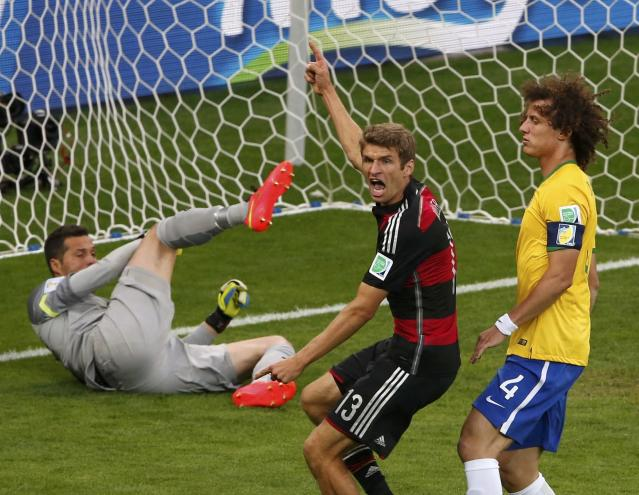 Germany's Thomas Mueller (C) celebrates past Brazil's David Luiz and goalkeeper Julio Cesar after scoring a goal during their 2014 World Cup semi-finals at the Mineirao stadium in Belo Horizonte July 8, 2014. REUTERS/David Gray (BRAZIL - Tags: SOCCER SPORT WORLD CUP TPX IMAGES OF THE DAY)