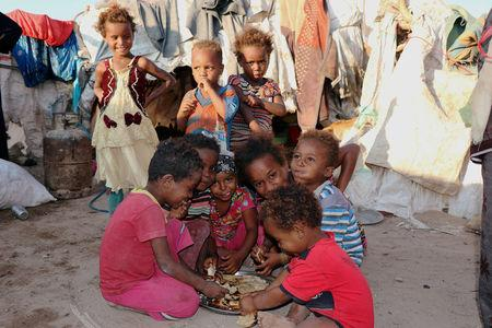 Children eat bread at a camp sheltering displaced people from the Red Sea port city of Hodeidah near Aden, Yemen