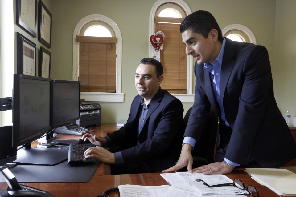 Certified financial planners Aaron Munoz, left, and Gilbert Cerda, pose for a photo at their offices in Downey, Calif. (Photo: AP Photo/Damian Dovarganes)