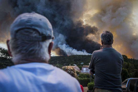 Fires burn around the picturesque hilltop town of Bormes-Les-Mimosas, France.
