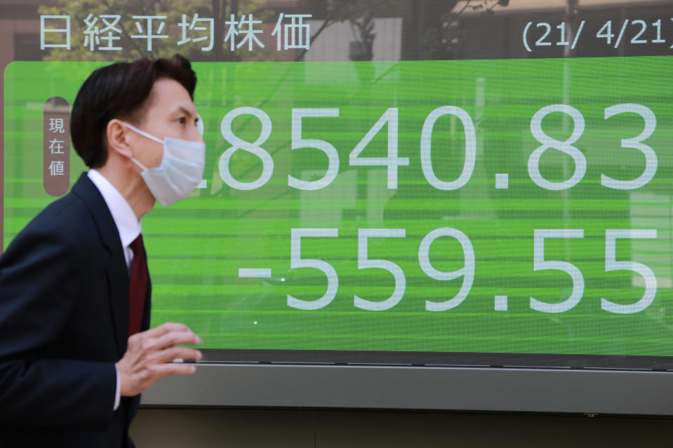 A man walks by an electronic stock board of a securities firm in Tokyo, Wednesday, April 21, 2021. Shares skidded in Asia on Wednesday after Wall Street closed lower for a second straight day, led by drops in technology companies and banks. (AP Photo/Koji Sasahara)