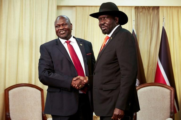 Handshake: President Salva Kiir (right) and his former vice president and rival, Riek Machar, pictured in Juba last October. The pair have until February 22 to form a coalition government scheduled under their 2018 peace accord. (AFP Photo/Alex McBride)