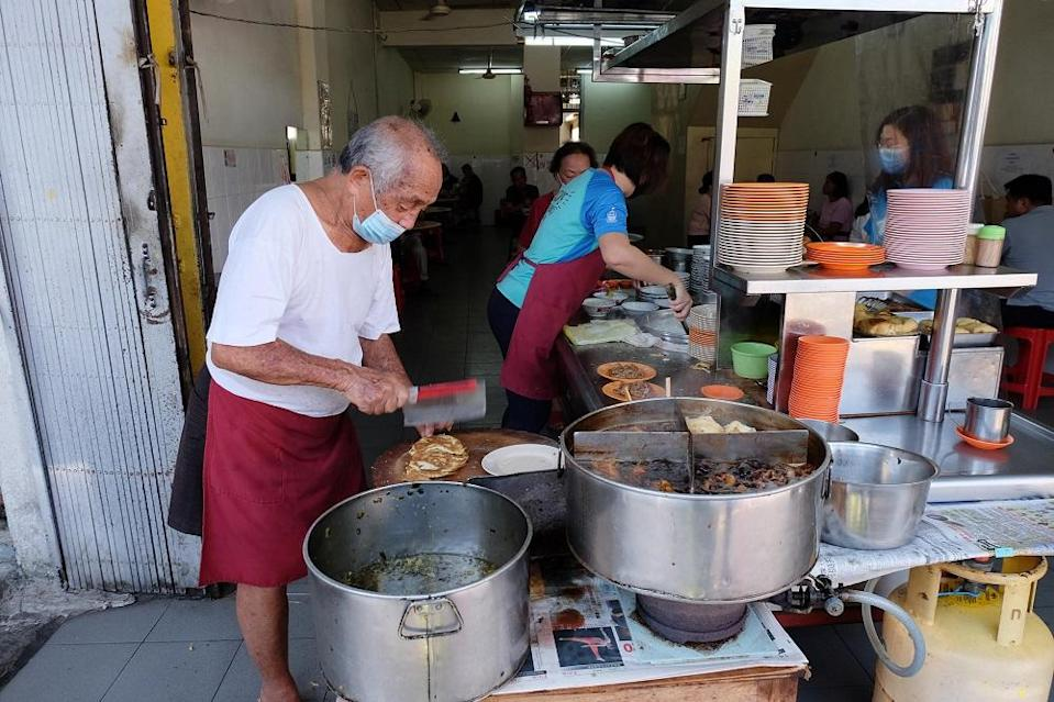 Ong Tai Buan prepares the side dishes to be served to customers at his stall placed prominently in front of the shop along Muntri Street in George Town February 24, 2021. — Pictures by Steven Ooi KE