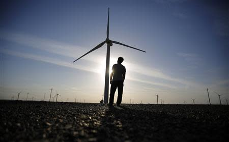 A worker stands as he looks at a wind turbine used to generate electricity, at a wind farm in Guazhou, 950km (590 miles) northwest of Lanzhou, Gansu Province September 15, 2013. REUTERS/Carlos Barria