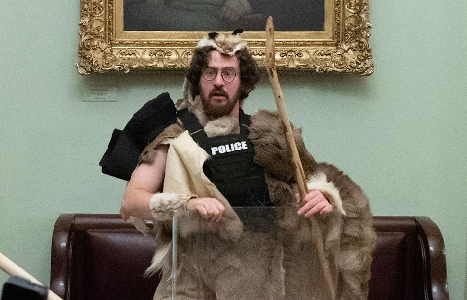 Aaron Mostofsky wears fur and grips a police riot shield, with no face mask, beneath an ornately framed painting
