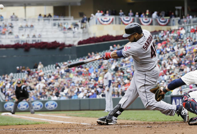Cleveland Indians' Carlos Santana hits a rwo-run home run off Minnesota Twins pitcher Cole DeVries in the fourth inning of a baseball game on Saturday, Sept. 28, 2013, in Minneapolis. (AP Photo/Jim Mone)