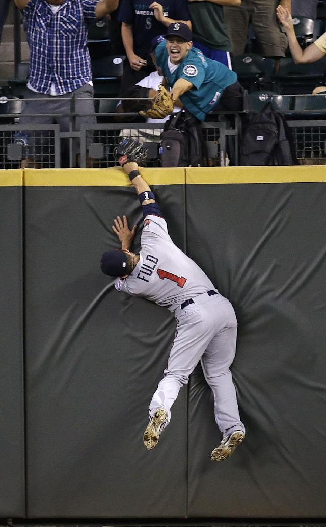 Minnesota Twins center fielder Sam Fuld slams into the outfield wall while chasing a deep fly ball from Seattle Mariners' Michael Saunders in the seventh inning of a baseball game Monday, July 7, 2014, in Seattle. Saunders had a home run on the play. (AP Photo/Elaine Thompson)