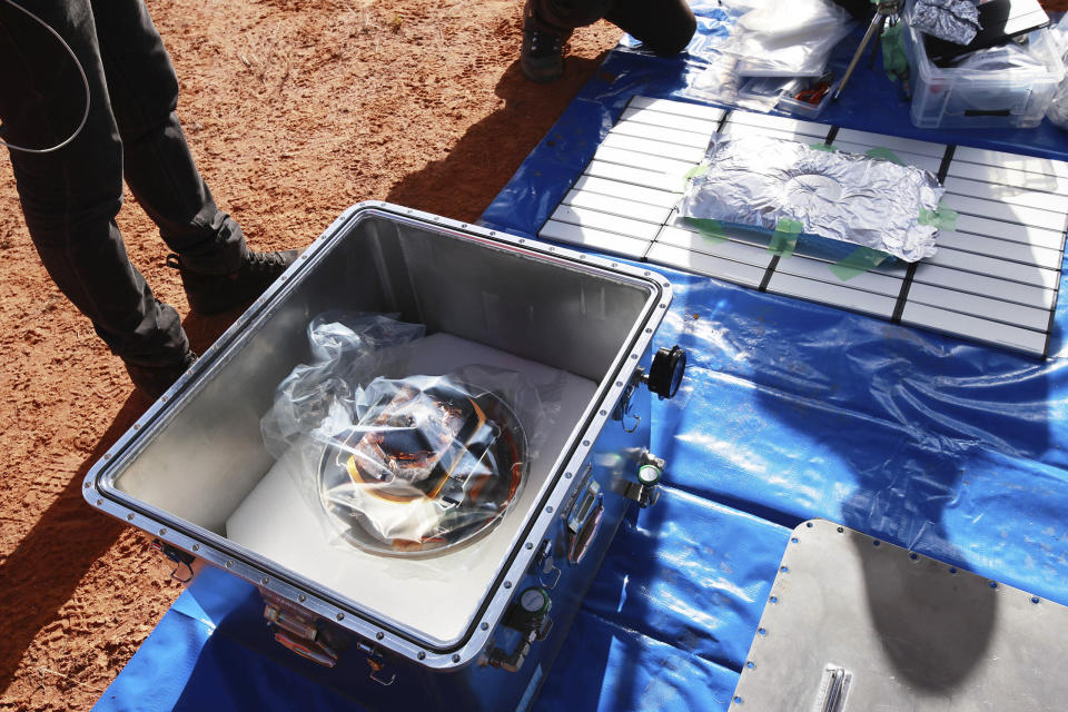 In this photo provided by the Japan Aerospace Exploration Agency (JAXA), members of JAXA retrieve a capsule dropped by Hayabusa2 in Woomera, southern Australia, Sunday, Dec. 6, 2020. A Japanese capsule carrying the first samples of asteroid subsurface shot across the night atmosphere early Sunday before successfully landing in the remote Australian Outback, completing a mission to provide clues to the origin of the solar system and life on Earth. (JAXA via AP)