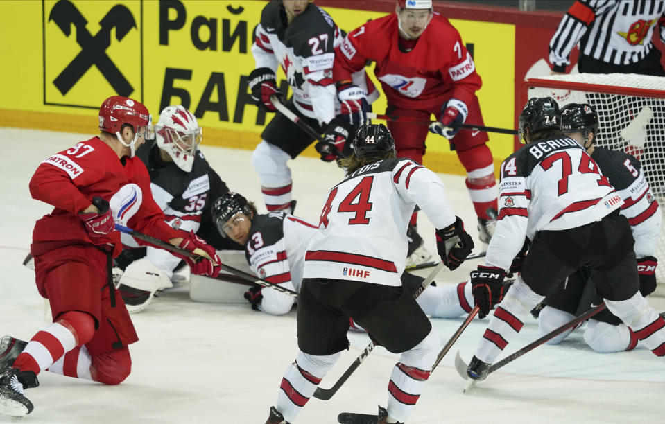 Yevgeni Timkin of Russia, left, scoring against Darcy Kuemper of Canada during the Ice Hockey World Championship quarterfinal match between Russia and Canada at the Olympic Sports Center in Riga, Latvia, Thursday, June 3, 2021. (AP Photo/Roman Koksarov)
