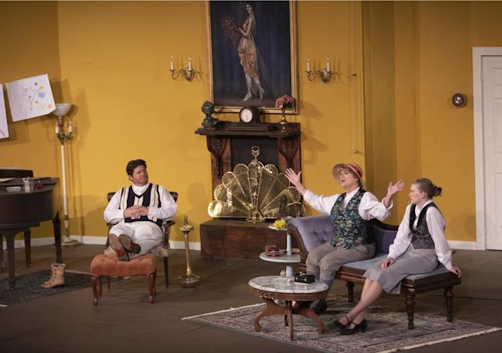 Three actors on stage, wearing period clothes