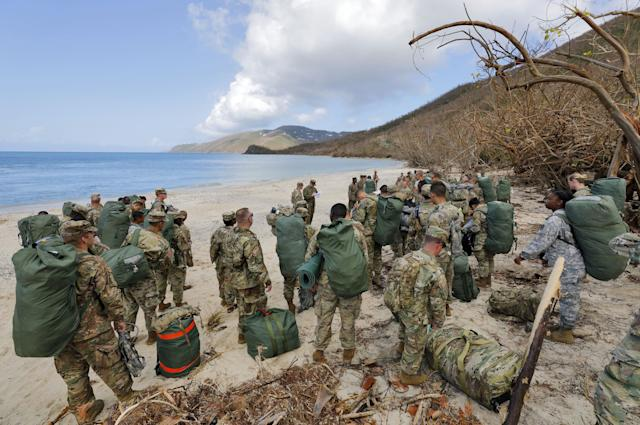 Army soldiers from the 602nd Area Support Medical Company gather on a beach as they await transport on a Navy landing craft while evacuating in advance of Hurricane Maria, in Charlotte Amalie, St. Thomas, U.S. Virgin Islands, Sept.17, 2017.