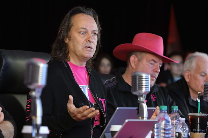 CEO John Legere, CFO Braxton Carter, and CTO Neville Ray sitting at a table behind microphones.