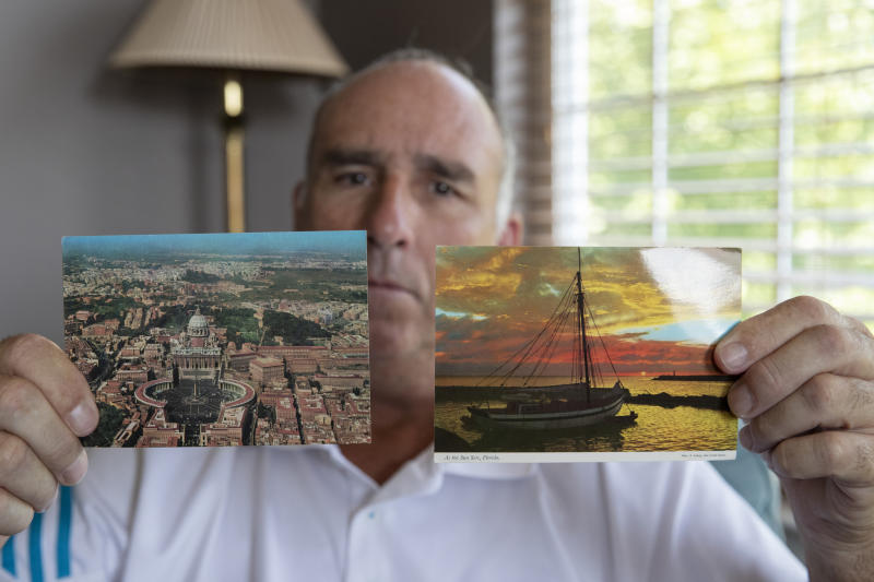 FILE - In this July 26, 2019, file photo, James Grein poses at home in Sterling, Va., with postcards from Florida and the Vatican sent to him as a boy by now-defrocked Cardinal Theodore McCarrick. Grein claims in a lawsuit in New Jersey that he told Pope John Paul II in 1988 about being sexually abused as a child by McCarrick but that the Vatican did nothing. (AP Photo/Manuel Balce Ceneta, File)