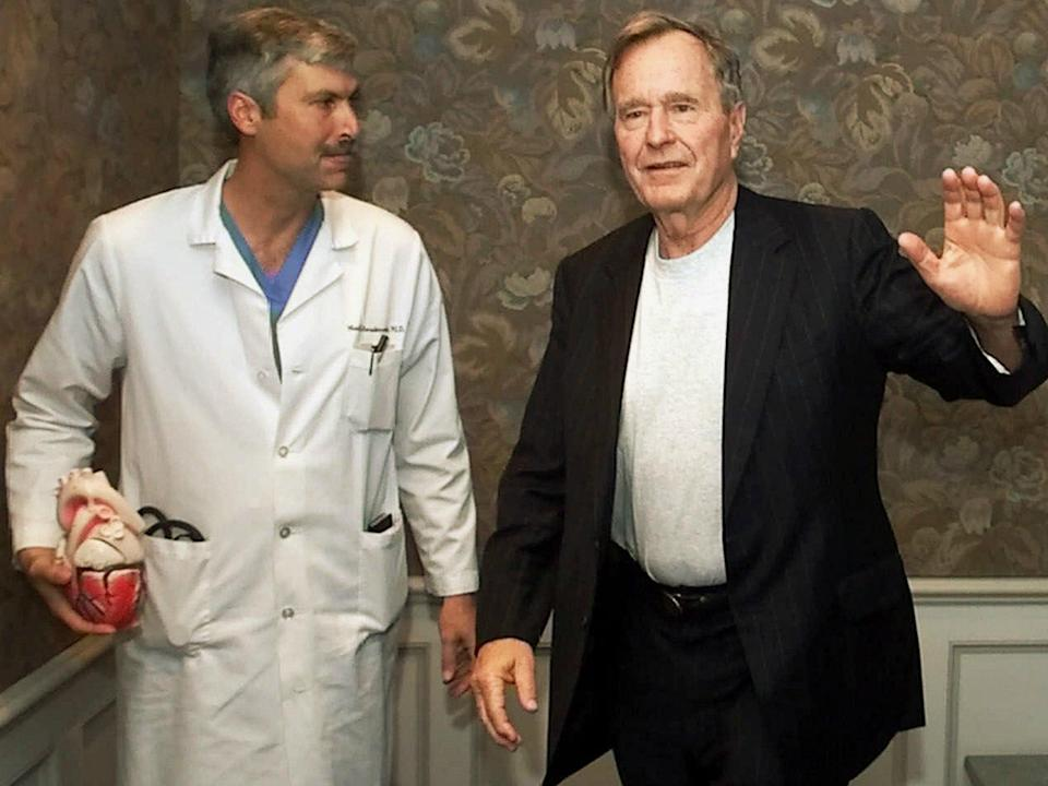 In this 25 February 2000 file photo, former President George HW Bush waves as he leaves Methodist Hospital with his cardiologist, Mark Hausknecht, who was killed in a bicycle drive-by shooting on 20 July 2018: AP Photo/David J. Phillip, File