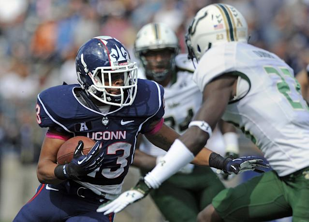 Connecticut running back Lyle McCombs (43) rushes for a 52-yard touchdown past South Florida defensive back Kenneth Durden (23) during the first half of an NCAA college football game in East Hartford, Conn., on Saturday, Oct. 12, 2013. (AP Photo/Fred Beckham)